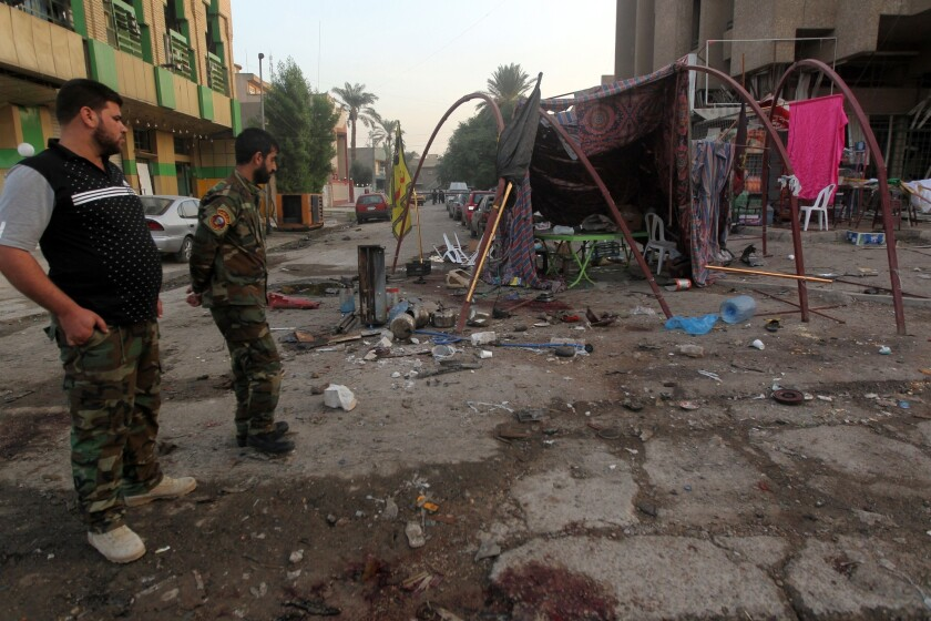 Iraqi security officers inspect the damage caused by an explosives-rigged vehicle on Baghdad's Palestine Street near a tent serving refreshments to Shiite pilgrims.