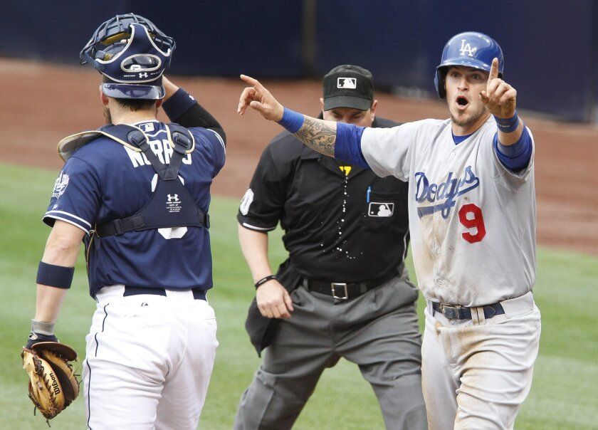 The Dodgers' Yasmani Grandal says he's safe after trying to score ahead of the tag by the Padres' catcher Derek Norris at home plate in the first inning.