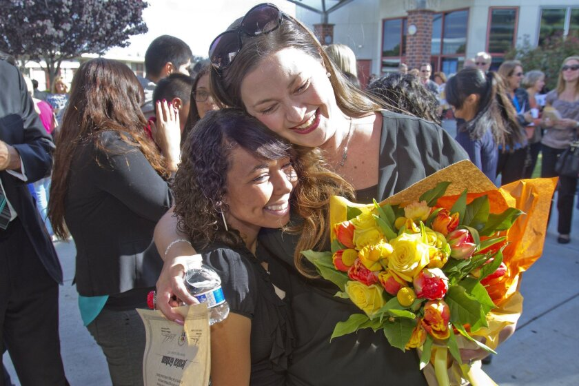 Jessica Graham, San Diego Unified's high school's teacher of the year,  is hugged by one of her students, Cierra Mosley, 11th grade, after Mosley sung a song Tuesday dedicated to Graham at the San Diego Unified School District Teacher of the Year Ceremony at Kearny High School.