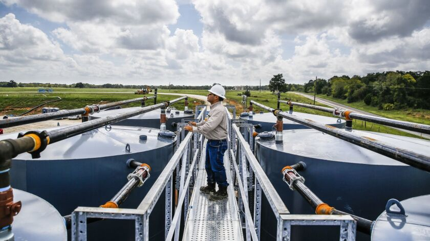 A worker stands between production tanks at a fracking site in October in Caldwell, Texas, on the northeastern edge of the Eagle Ford Shale.