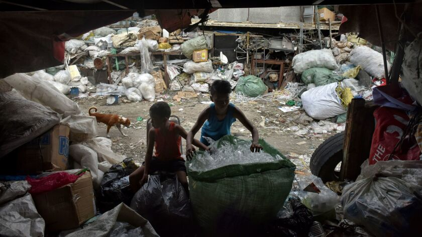 In this file photo, children sort waste products in an impoverished community in Manila.