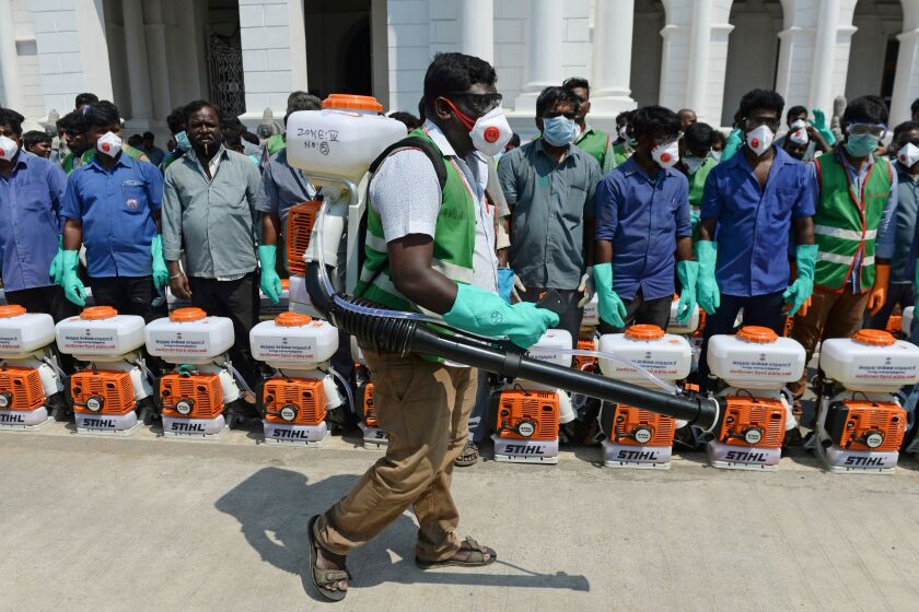 Health workers prepare to spray disinfectant outside municipal offices in Chennai, India