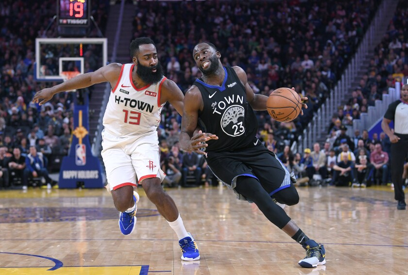 Warriors forward Draymond Green tries to drive past Rockets guard James Harden during an NBA game on Dec. 25, 2019, in San Francisco.