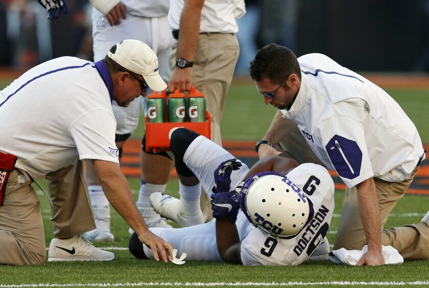 TCU wide receiver Josh Doctson (9) holds his wrist as he is attended to following an injury in the second quarter of an NCAA college football game against Oklahoma State in Stillwater, Okla., Saturday, Nov. 7, 2015. (AP Photo/Sue Ogrocki)