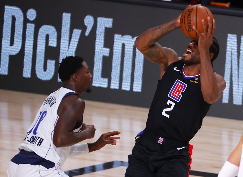 Clippers forward Kawhi Leonard draws a foul from Dallas Mavericks forward Dorian Finney-Smith during the second quarter.