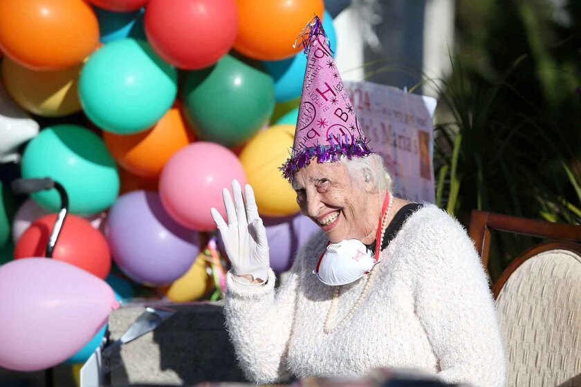 Maria Siani waves to friends and family as she is greeted with a drive-by surprise 96th-birthday party in front of her home in Laguna Beach on Wednesday.
