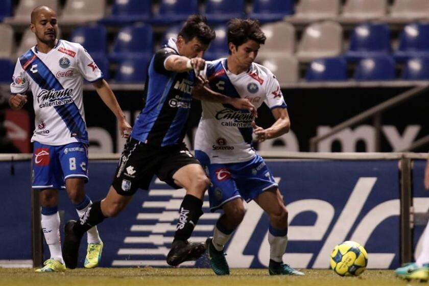 Edgar Benítez (i) de Gallos Blancos de Querétaro disputa el balón contra Carlos Orrantía (d) del Puebla FC. EFE/Archivo