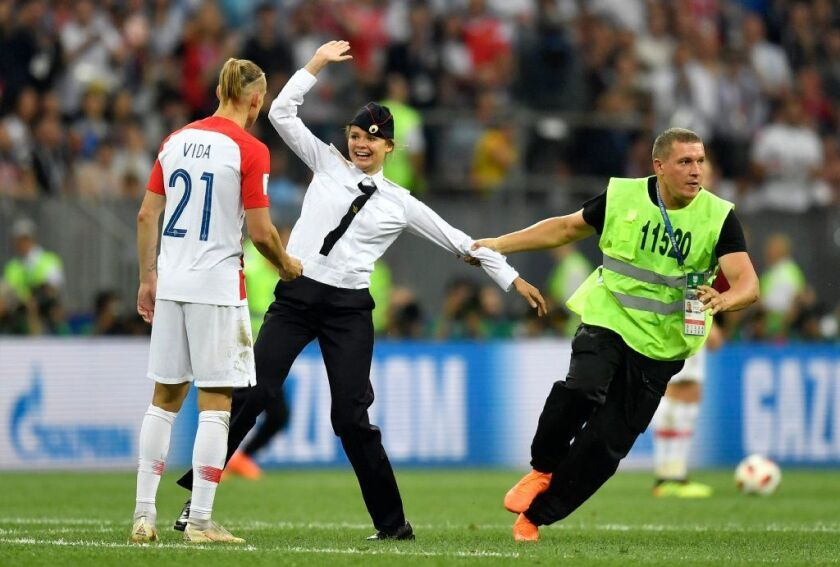 Stewards pull a member of Pussy Riot away from the field during Sunday's World Cup final in Moscow.