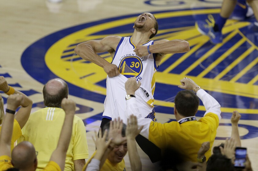 Fans cheer as Warriors guard Stephen Curry yells following Golden State's 96-88 victory over the Thunder in Game 7.
