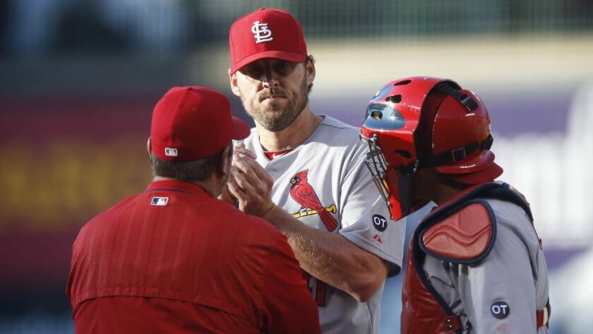 St. Louis Cardinals pitching coach Derek Lilliquist, left, speaks with pitcher John Lackey, center, and catcher Yadier Molina during a game against the Colorado Rockies on June 8.