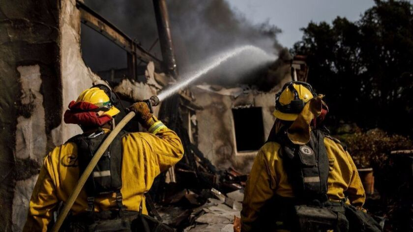 Humboldt County firefighters Bobby Gray, left, hoses down smoldering flames inside a destroyed home, as Kellee Stoehr, right looks on, after the Thomas Fire burned in Montecito.
