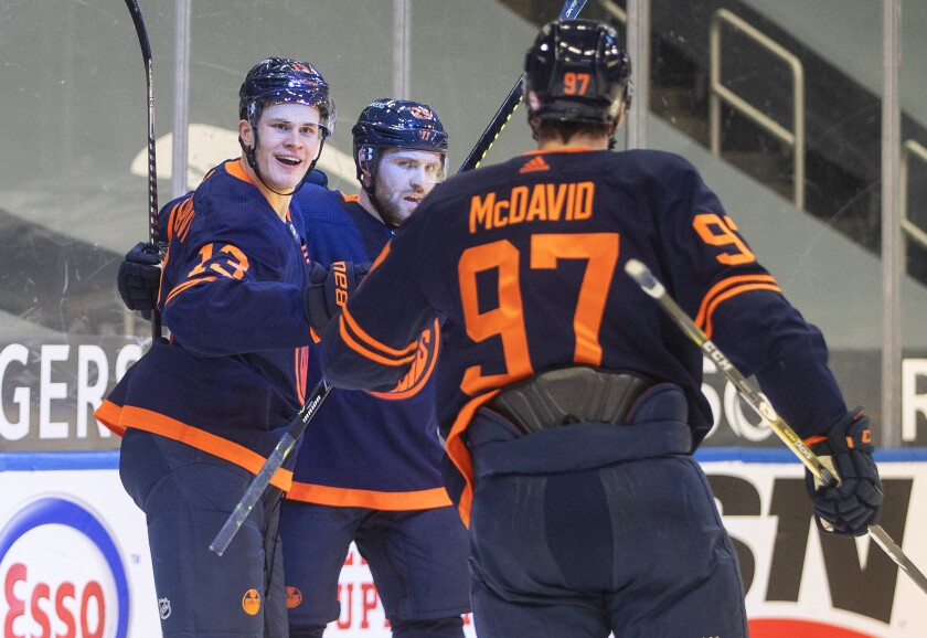 Edmonton Oilers' Jesse Puljujarvi (13), Leon Draisaitl (29) and Connor McDavid (97) celebrate a goal against the Calgary Flames during the second period of an NHL hockey game Saturday, March 6, 2021, in Edmonton, Alberta. (Jason Franson/The Canadian Press via AP)