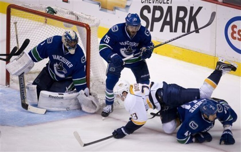 Nashville Predators left wing Zach Boychuk (23) tries to get a shot past Vancouver Canucks defenseman Andrew Alberts (41), center Andrew Ebbett (25) and goalie Roberto Luongo (1) during third period NHL hockey action in Vancouver Thursday March 14, 2013. (AP Photo/The Canadian Press, Jonathan Hayward)