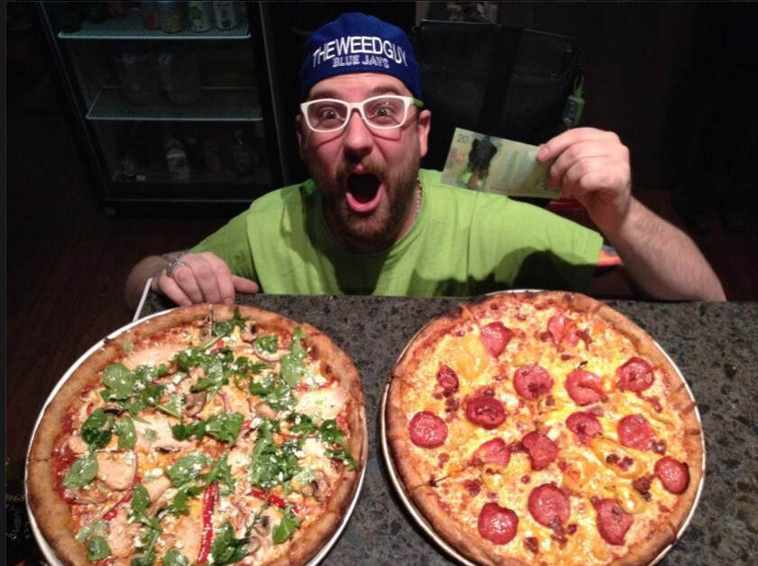 Mega Ill owner Mark Klokeid poses with two pizzas. The Vancouver pizza restaurant will put pot on your pizza -- provided you have a cannabis card.
