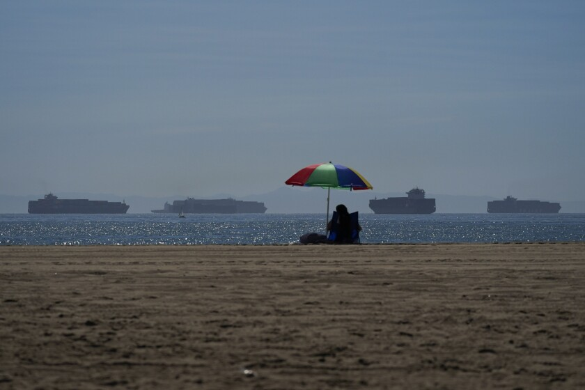A person lounges on a beach in Seal Beach as container ships wait to dock.