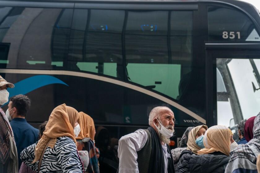 افراد تخلیه شده با ظاهر خسته برای سوار شدن به اتوبوس صف می گیرند