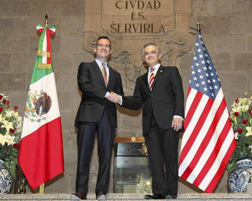"""Los Angeles Mayor Eric Garcetti, left, meets with his Mexico City counterpart, Miguel Angel Mancera. Garcetti used his """"good community meeting Spanish"""" in interviews with the Mexican press corps."""