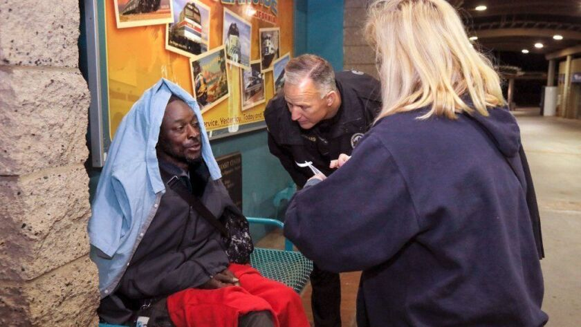 Volunteer Michelle Gomez and Oceanside Police Officer Steve Peppard interview Barry Jones, a homeless man who was sleeping on a bench at the Oceanside Transit Center.