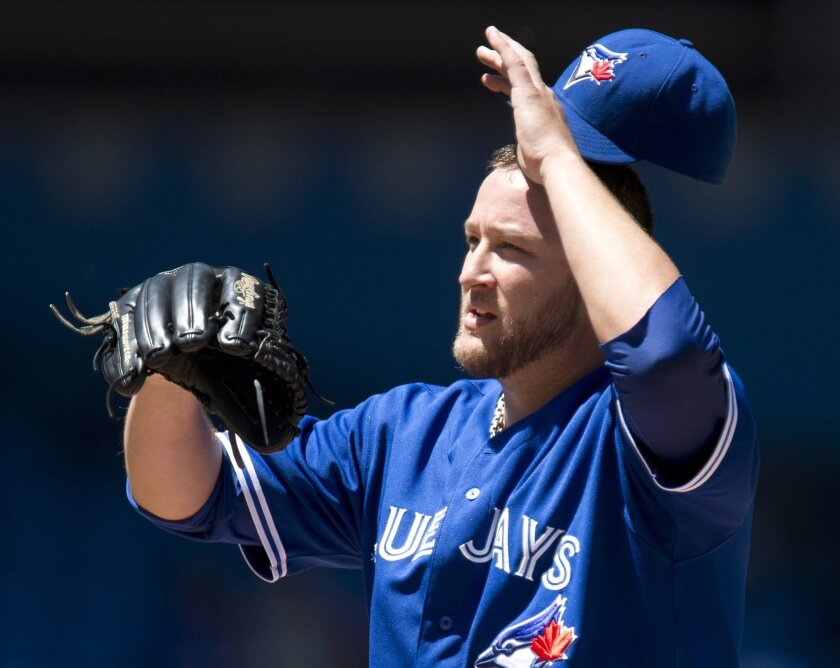 Toronto Blue Jays starting pitcher Mark Buehrle adjusts his cap during a baseball game against the St. Louis Cardinals in Toronto, Saturday, June 7, 2014. (AP Photo/The Canadian Press, Frank Gunn)