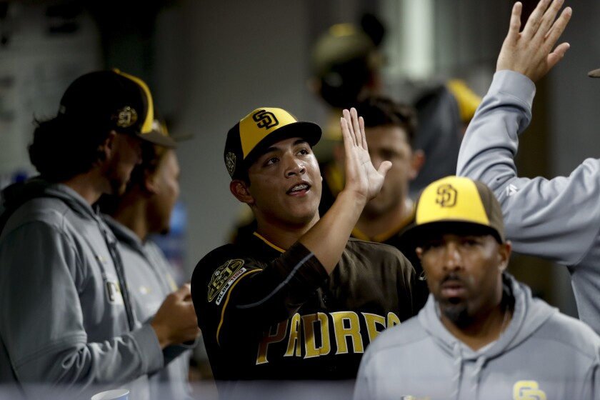 Padres relief pitcher Andres Munoz, center, is greeted in the dugout during the sixth inning of the team's baseball game against the Atlanta Braves, Friday, July 12.