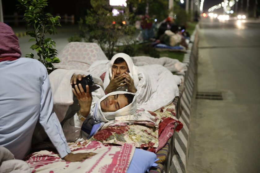 People sleep outside on a street in Katmandu, Nepal, following a massive earthquake on April 25.