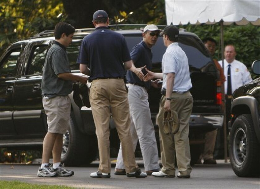 President Barack Obama, center, shakes hands with his golf partners outside of the main residence of the White House, Sunday, May 31, 2009 in Washington. The President was returning from Fort Belvoir where he played golf. (AP Photo/Pablo Martinez Monsivais)