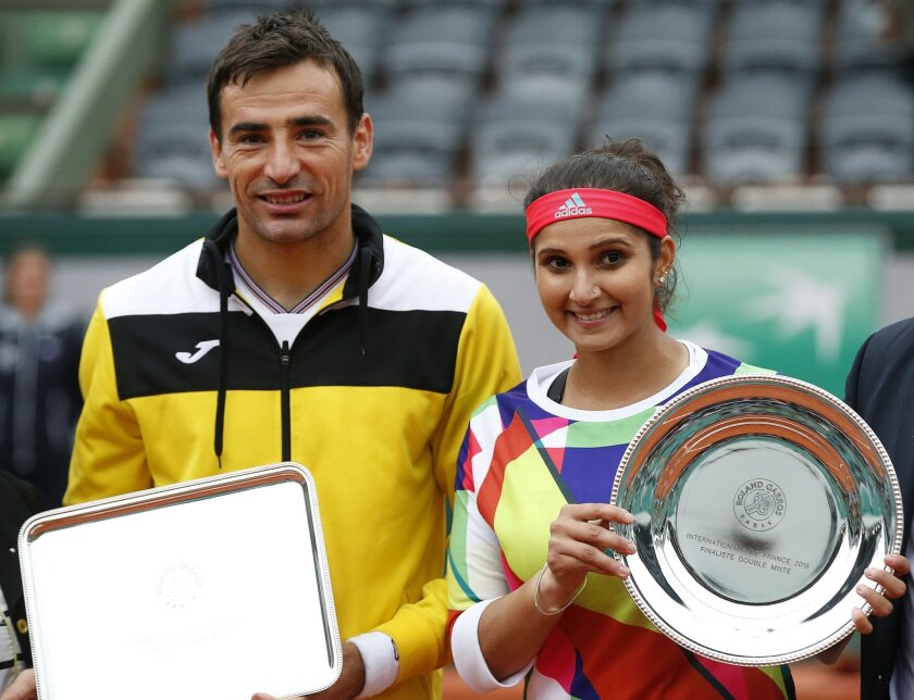 India's Sania Mirza and Croatia's Ivan Dodic, left, hold the runner-up trophy after losing to Switzerland's Martina Hingis and India's Leander Paes in the mixed doubles final of the French Open tennis tournament at the Roland Garros stadium in Paris, France, Friday, June 3, 2016. (AP Photo/Alastair