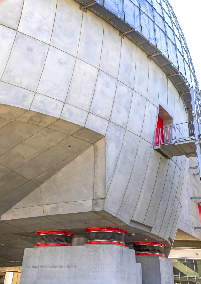 Base isolators, red and black circular forms at the base of the new Academy Museum's sphere, are left exposed.