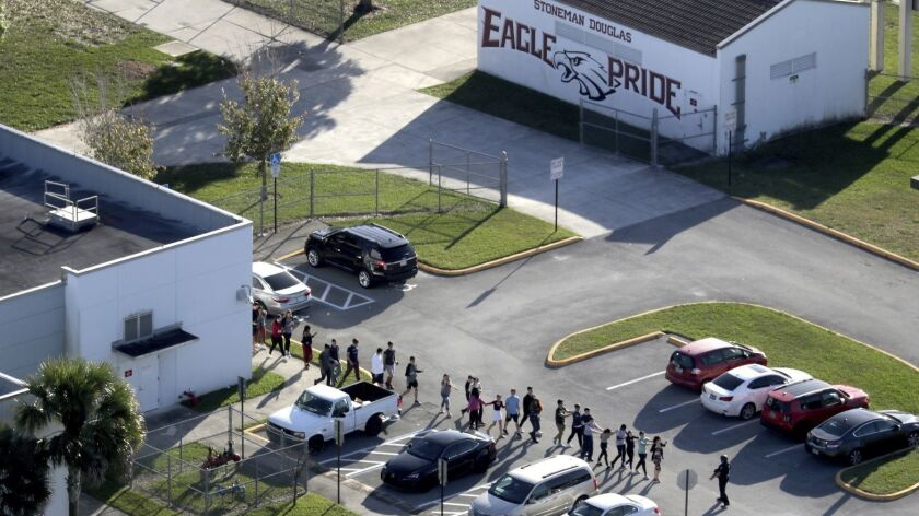 FILE - In this Feb. 14, 2018 file photo. students are evacuated by police from Marjory Stoneman Doug