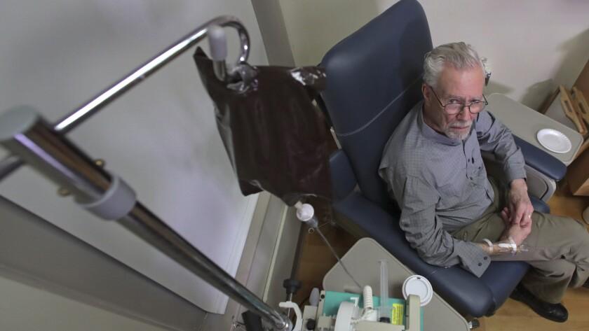 A man sits in a chair receiving an intravenous drip