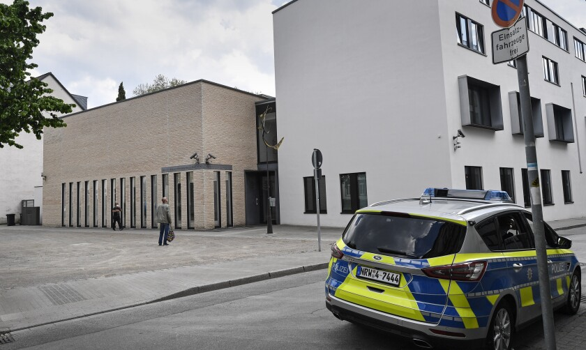 """A police car stands in front of the synagogue in Gelsenkirchen, Germany, Thursday, May 13, 2021. Germany's leading Jewish group has sharply condemned protests in front of a synagogue in the western city of Gelsenkirchen as """"pure antisemitism."""" The Central Council of Jews in Germany on Thursday tweeted a video of dozens of protesters waving Palestinian and Turkish flags and yelling expletives about Jews. (AP Photo/Martin Meissner)"""