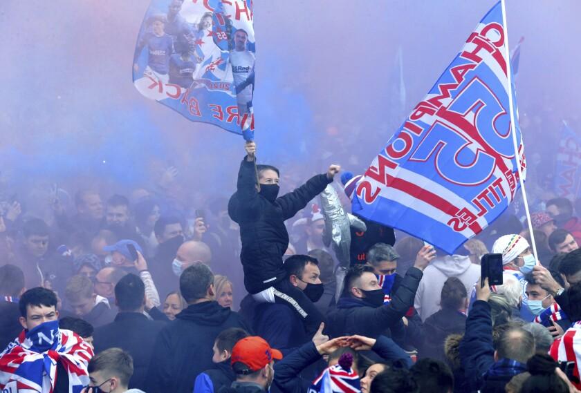 Rangers soccer fans defy pandemic restrictions to celebrate winning the Scottish Premiership title, outside the Ibrox Stadium in Glasgow, Scotland, Sunday March 7, 2021. Rangers took their 55th domestic league title, their first Scottish Premiership title in 10 years, after Celtic failed to beat Dundee United on Sunday. (Robert Perry/PA via AP)