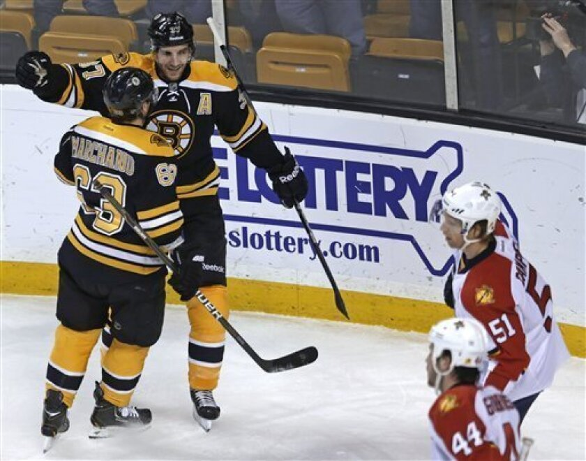 Boston Bruins center Patrice Bergeron is congratulated by teammate Brad Marchand (63) after his goal against the Florida Panthers during the first period of an NHL hockey game in Boston, Thursday, March 14, 2013. At right are Florida Panthers defensemen Erik Gudbranson (44) and Brian Campbell (51). Bergeron had two goals in the Bruins' 4-1 win. (AP Photo/Charles Krupa)