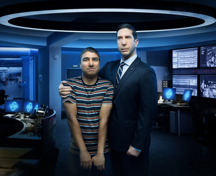 """This image released by Peacock shows Nick Mohammed, left, and David Schwimmer from the series """"Intelligence,"""" which will be available on the new streaming service Peacock, launching Wednesday. (Peacock via AP)"""