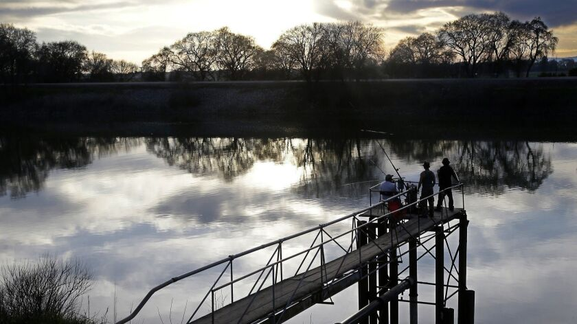 In this Tuesday, Feb. 23, 2016 photo, people try to catch fish along the Sacramento River in the San