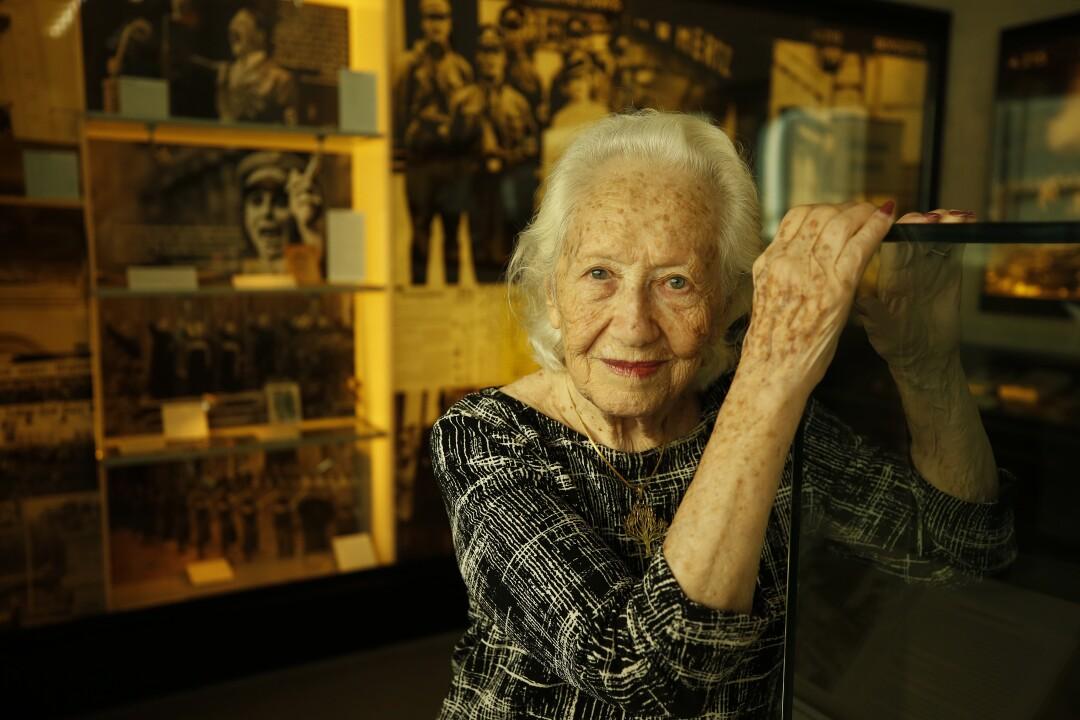 Une femme pose avec ses mains au sommet d'une vitrine en verre.  Derrière elle, des images et des artefacts historiques sont exposés.