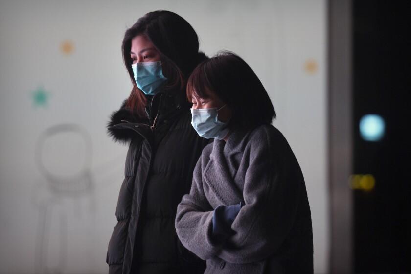 Unas personas portan mascarillas para protegerse contra el coronavirus en Beijing, el miércoles 13