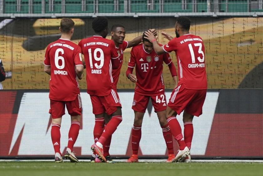 El jugador de Bayern Jamal Musiala, segundo desde la derecha, es felicitado por sus compañeros tras anotar el tercer gol del equipo en una victoria de 3-2 sobre Wolfsburg en la Bundesliga el sábado, 17 de abril del 2021. (AP Foto/Michael Sohn)