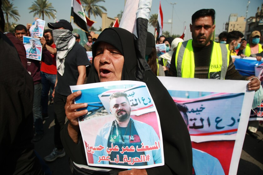 """A woman holds a picture of her a missing son during anti-government protest in Baghdad, Iraq, Sunday, Feb. 23, 2020. There are 25 activists still missing since the protests erupted on Oct. 1, 2019, according to the semi-official Iraqi High Commission for Human Rights. No group has claimed responsibility but activists have blamed the militias. Arabic reads, """"Freedom for paramedic Omr Ali."""" (AP Photo/Khalid Mohammed)"""