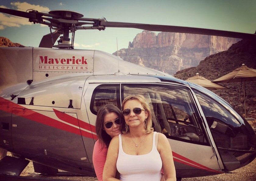 In this Oct. 21, 2014, photo, Brittany Maynard, left, hugs her mother, Debbie Ziegler, next to a helicopter at the Grand Canyon National Park in Arizona.
