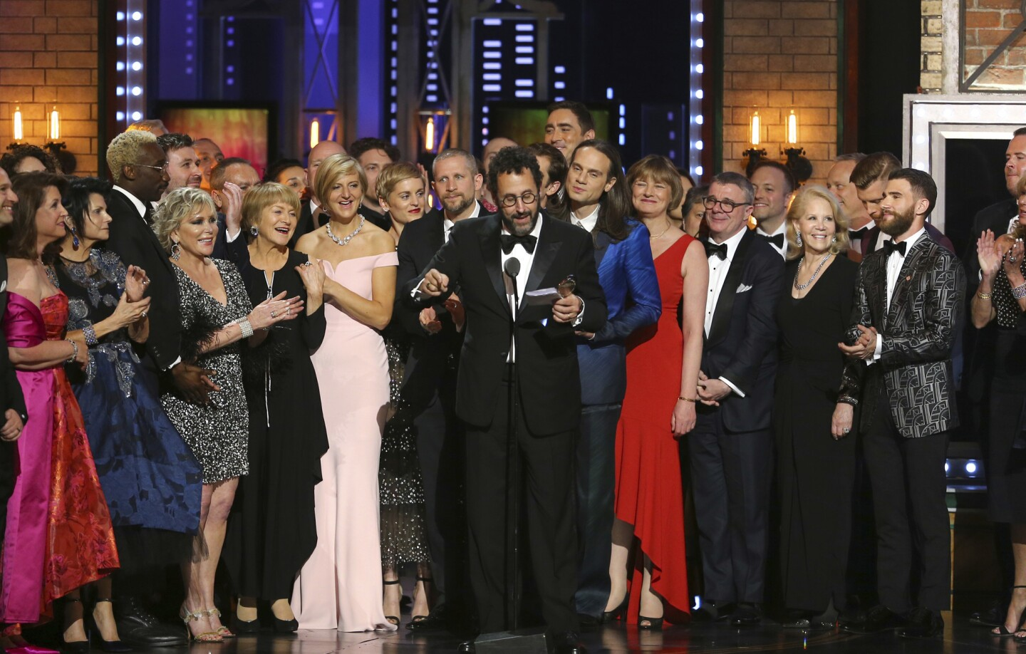 """Playwright Tony Kushner, center, and the cast and crew of """"Angels in America"""" accept the award for best revival of a play at the 72nd Tony Awards."""