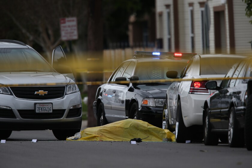 A body lies at the scene where two Santa Ana police officers were involved in a shooting that left one man dead in the 1000 block of West 3rd Street on Friday, Feb. 27.