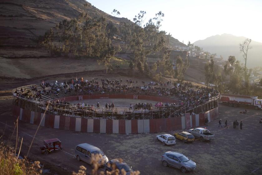 ARCHIVO - En esta fotografía de archivo del 16 de julio de 2013, personas celebran una corrida de toros en Lachaqui, Perú. Una decisión judicial del 16 de septiembre de 2021 prohibió entrenar a los niños en esa práctica. (AP Foto/Martín Mejía, archivo)