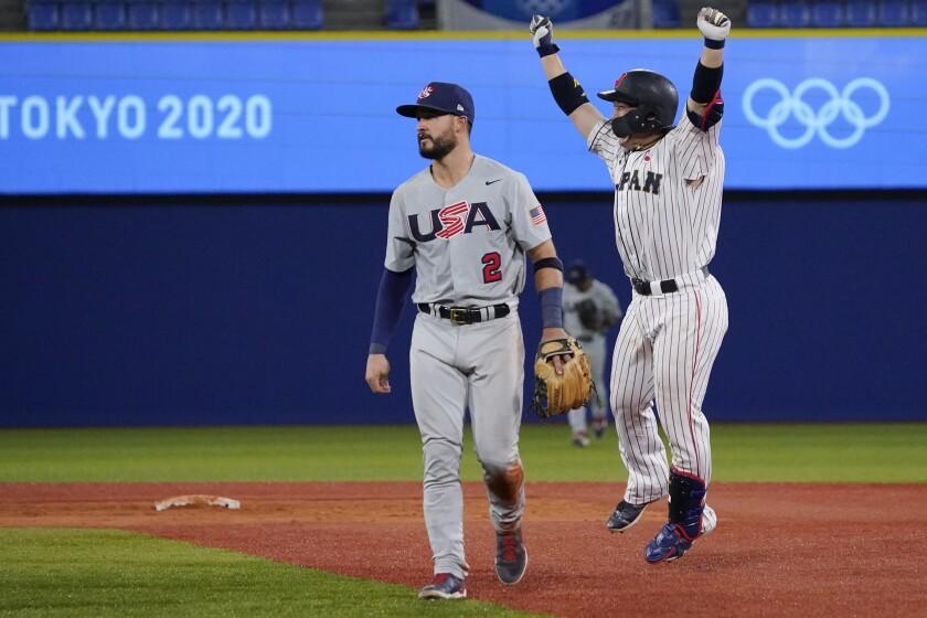 Japan's Takuya Kai, right, celebrate past United States' Eddy Alvarez after a baseball game at the 2020 Summer Olympics, Monday, Aug. 2, 2021, in Yokohama, Japan. Japan won 7-6. (AP Photo/Sue Ogrocki)