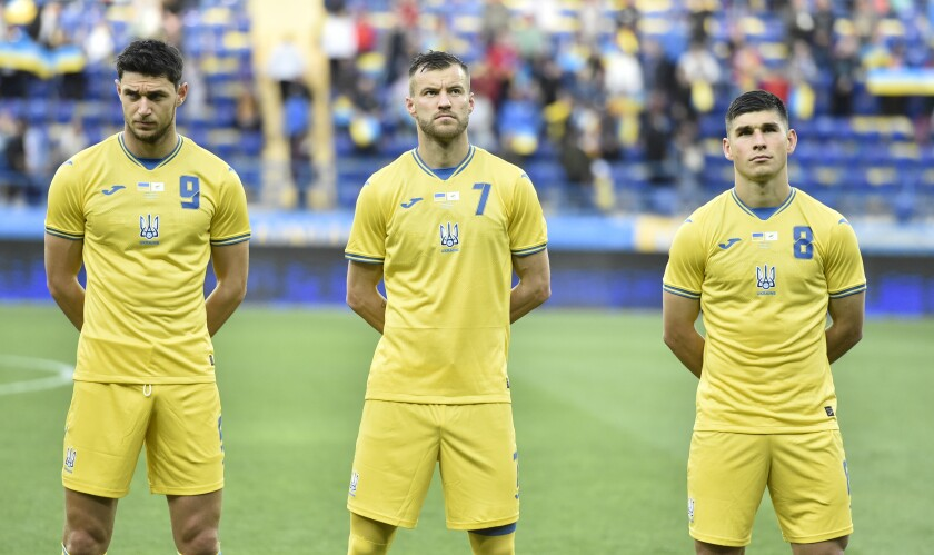 """Ukraine's Roman Yaremchuk, left, Andriy Yarmolenko, center, and Ruslan Malinovskyi stand in a new kit for Ukraine's soccer team that shows a map including Russian-annexed Crimea before the international friendly soccer match between Ukraine and Cyprus in Kharkiv, Ukraine, Monday, June 7, 2021. Russian officials and lawmakers have denounced the design of the Ukrainian national soccer team's shirt for this month's European Championship. The yellow-and-blue Ukrainian uniform features a map of the country that includes Crimea and the slogan """"Glory to Ukraine!"""". The Black Sea peninsula was annexed by Russia in 2014 following the ouster of its Moscow-friendly president. Most of the world hasn't acknowledged the annexation. (AP Photo)"""