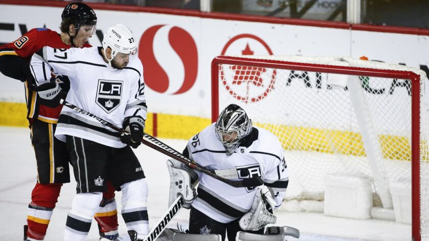Kings goalie Jack Campbell, right, and teammate Alec Martinez, center, keep Calgary Flames' Matthew Tkachuk away from the net during the second period.