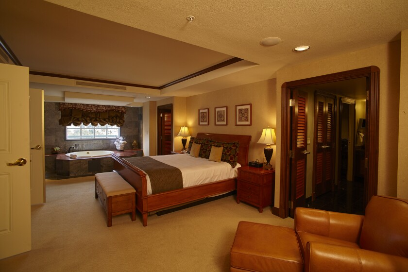 The master bedroom in this Barona hotel suite has a whirlpool tub and his and hers master bathrooms, with walk-in closets.