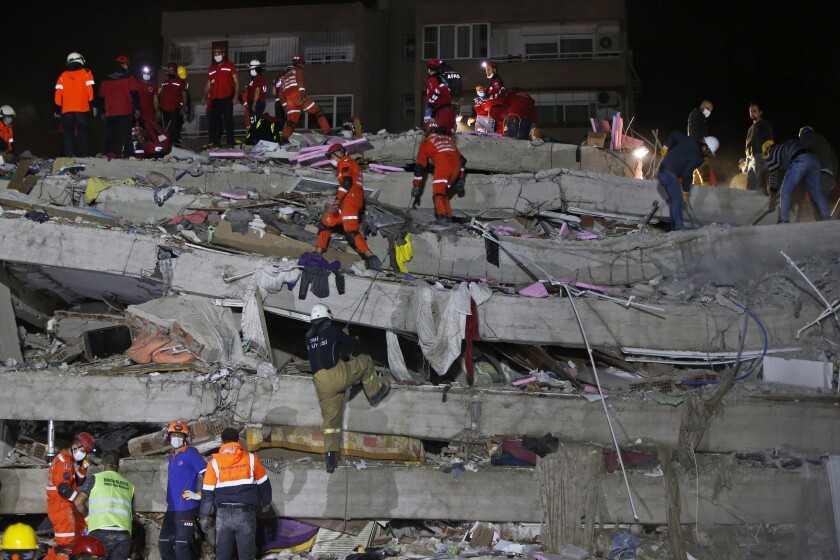 Rescue workers and local people carry a wounded person found in the debris of a collapsed building, in Izmir, Turkey