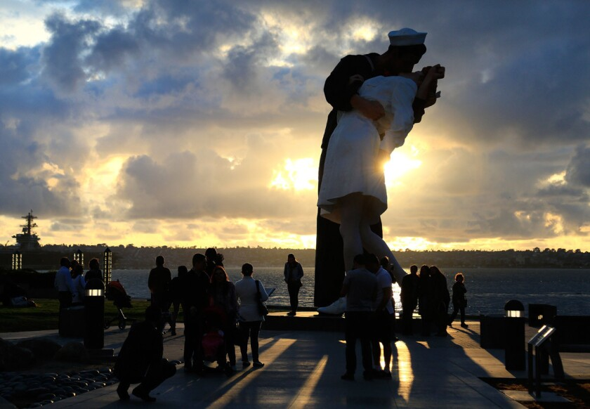 """People come to San Diego Harbor to watch the sunset at the """"Unconditional Surrender"""" statue on Friday evening."""