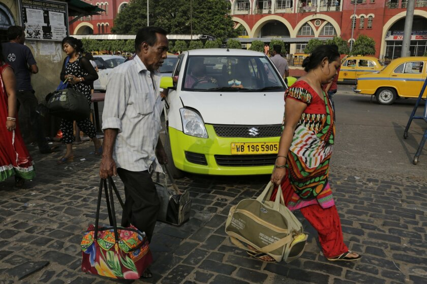 In this March 29, 2016 photo, Indian commuters walk past a parked Ola cab in Kolkata, India. Aiming to wrest control of India's booming taxi market, two cab-hailing smartphone apps _ Uber and Ola _ are promising hundreds of millions in new investment while also facing off with one another in court. (AP Photo/ Bikas Das)
